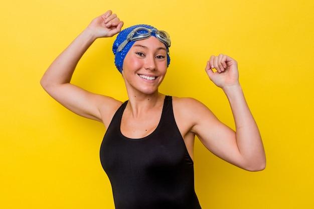 特別な日を祝う黄色の背景に孤立した若いオーストラリアの水泳選手の女性は、エネルギーでジャンプして腕を上げます。