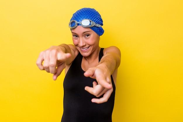 Женщина молодой австралийский пловец, изолированные на желтом фоне веселые улыбки, указывая на фронт.