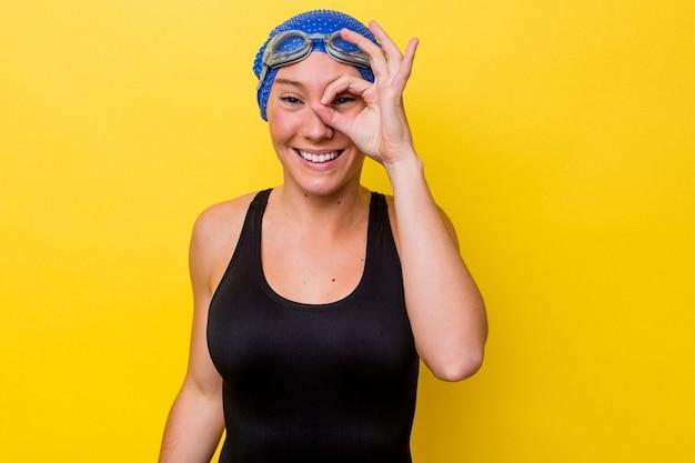 노란색 배경에 고립 된 젊은 호주 수영 여자 눈에 확인 제스처를 유지 흥분.
