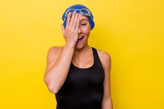 Молодая австралийская женщина-пловец изолирована на желтом фоне с удовольствием, покрывая половину лица ладонью.