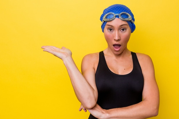 黄色の背景に分離された若いオーストラリアのスイマーの女性は、手のひらにコピースペースを保持していることに感銘を受けました。