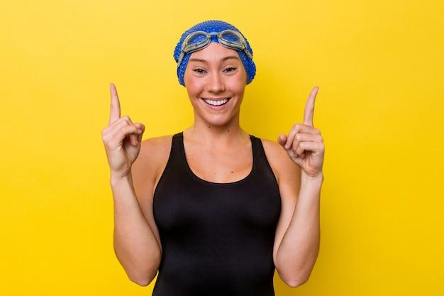 노란색 배경에 고립 된 젊은 호주 수영 여자는 빈 공간을 보여주는 두 앞 손가락으로 나타냅니다.