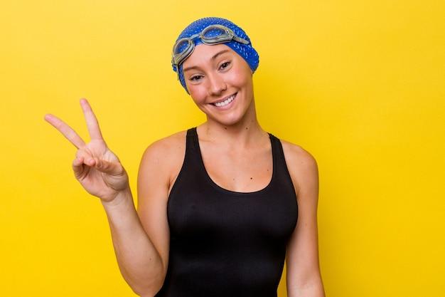 黄色の背景に分離された若いオーストラリアのスイマー女性は、指で平和のシンボルを示して楽しくてのんきです。