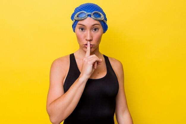 Молодая австралийская женщина-пловец изолирована на желтом фоне, храня в секрете или прося молчания.