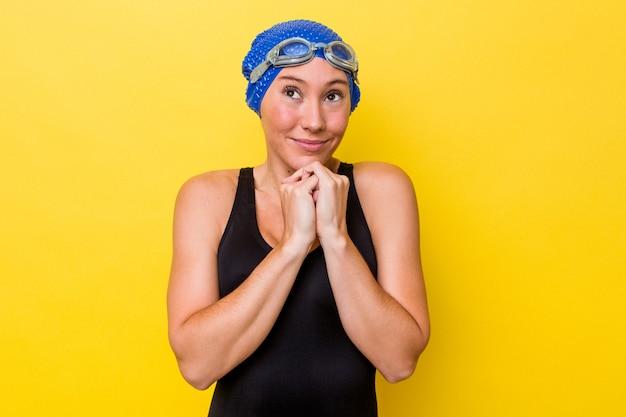 黄色の背景で隔離された若いオーストラリアの水泳選手の女性は、あごの下に手を保ち、幸せそうに脇を探しています。