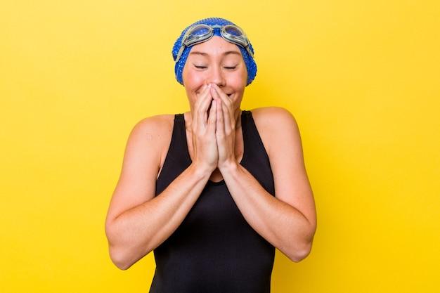 黄色の背景に孤立した若いオーストラリアの水泳選手の女性は、手で口を覆って、何かについて笑っています。
