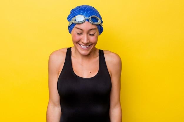 黄色の背景に孤立した若いオーストラリアの水泳選手の女性は笑って目を閉じ、リラックスして幸せな気分になります。