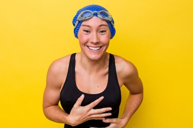 Молодая австралийская женщина-пловец, изолированная на желтом фоне, счастливо смеется и веселится, держа руки на животе.