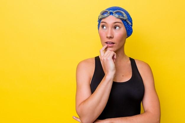 Молодая австралийская женщина-пловец изолирована на желтом фоне, смотрит в сторону с сомнительным и скептическим выражением лица.