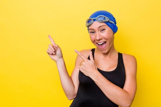 興奮と欲望を表現し、コピースペースに人差し指で指している黄色の背景に分離された若いオーストラリアの水泳選手の女性。
