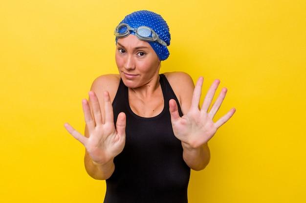 Молодая австралийская женщина-пловец изолирована на желтом фоне, отвергая кого-то, показывая жест отвращения.