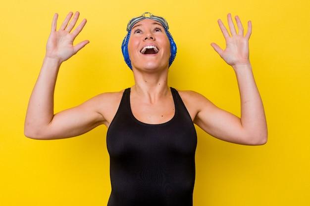 黄色の背景に孤立した若いオーストラリアの水泳選手の女性が空に向かって叫び、見上げて、欲求不満。