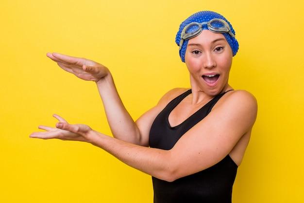 Молодая австралийская женщина-пловец, изолированная на желтом фоне, потрясена и поражена, держа в руках копию пространства.