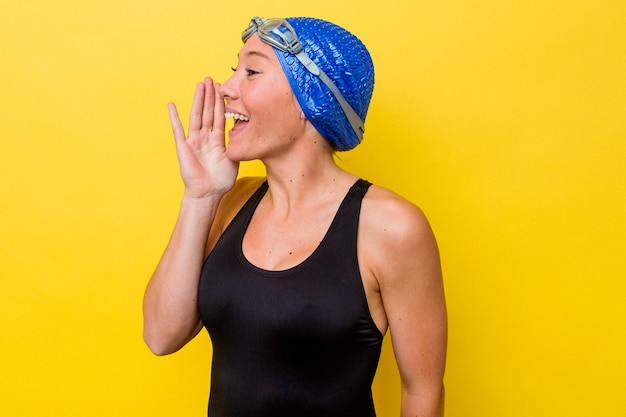 開いた口の近くで叫び、手のひらを保持している黄色の背景に分離された若いオーストラリアのスイマー女性。