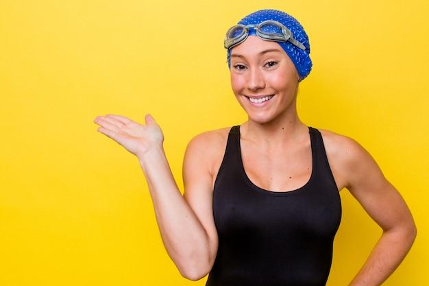 手のひらにコピースペースを示し、腰に別の手を保持している黄色の背景に分離された若いオーストラリアの水泳選手の女性。