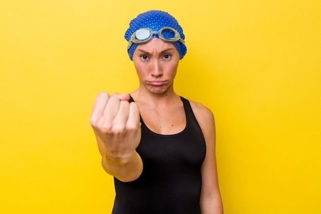 Молодая австралийская женщина-пловец изолирована на желтом фоне, показывая кулак на камеру, агрессивное выражение лица.