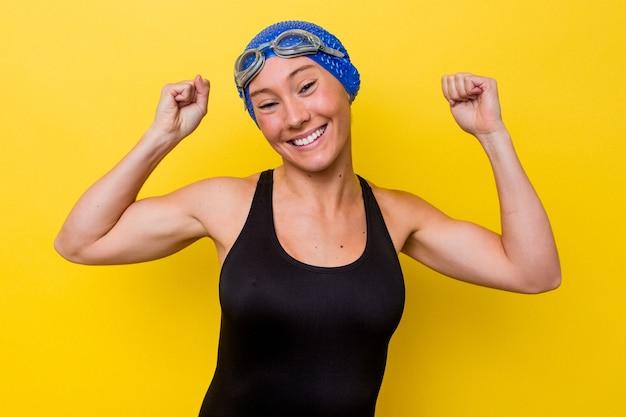 女性の力の象徴である腕で強さのジェスチャーを示す黄色の背景に分離された若いオーストラリアのスイマー女性