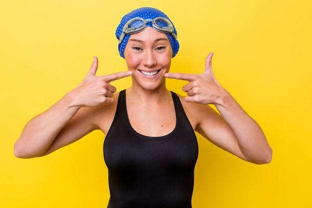 입에서 손가락을 가리키는 노란색 배경 미소에 고립 된 젊은 호주 수영 여자.
