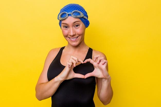 笑顔と手でハートの形を示す黄色の背景に分離された若いオーストラリアのスイマー女性。