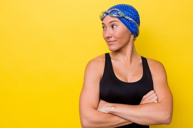 腕を組んで自信を持って笑って黄色の背景に分離された若いオーストラリアのスイマー女性。