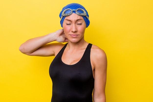 座りがちな生活のために首の痛みに苦しんでいる黄色の背景に分離された若いオーストラリアのスイマー女性。