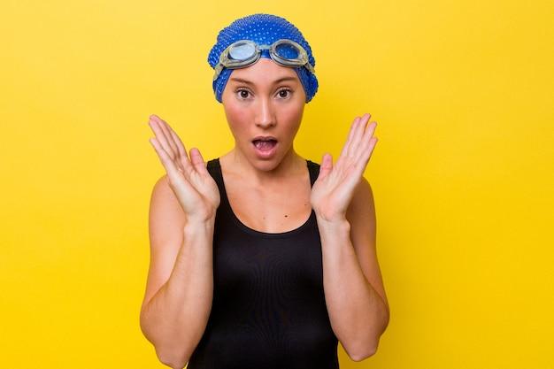 黄色の背景に分離された若いオーストラリアの水泳選手の女性は驚いてショックを受けました。