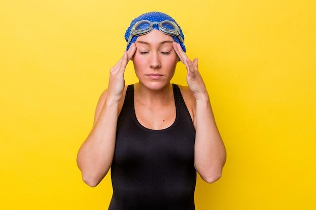 Молодая австралийская женщина-пловец изолирована на желтом фоне, трогательно висков и имея головную боль.