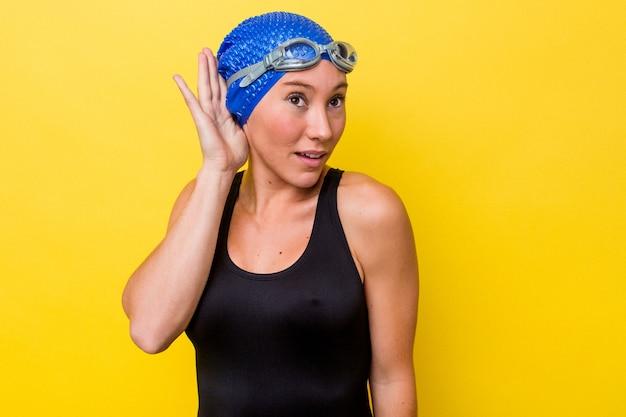 ゴシップを聴こうとしている黄色の背景に分離された若いオーストラリアの水泳選手の女性。
