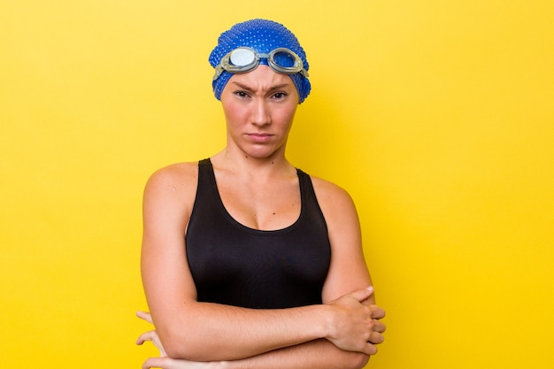 皮肉な表情でカメラを見て不幸な黄色の背景に分離された若いオーストラリアの水泳選手の女性。