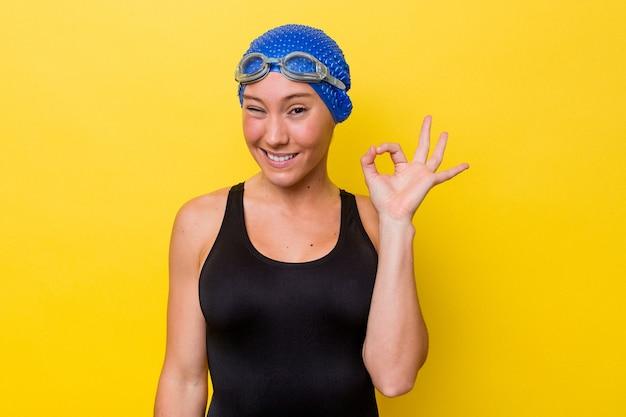 노란색 배경에 격리된 젊은 호주 수영 여성은 눈을 윙크하고 손으로 괜찮은 몸짓을 합니다.
