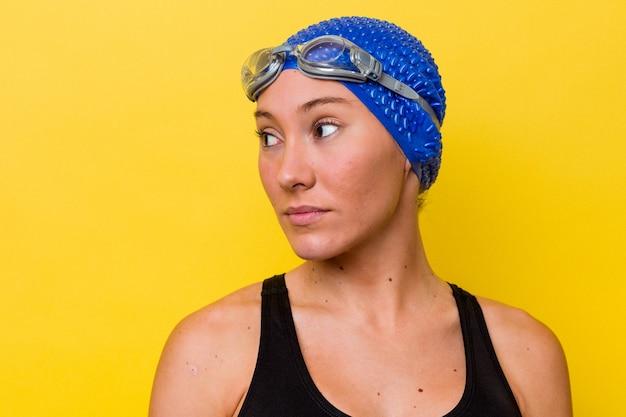 노란색 배경에 고립 된 젊은 호주 수영 여자