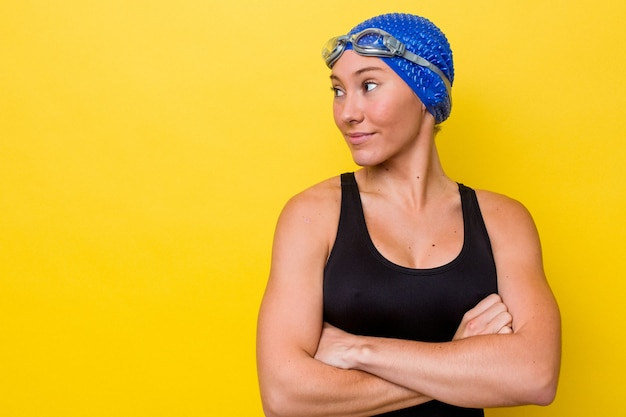 Young australian swimmer woman isolated on yellow background smiling confident with crossed arms.