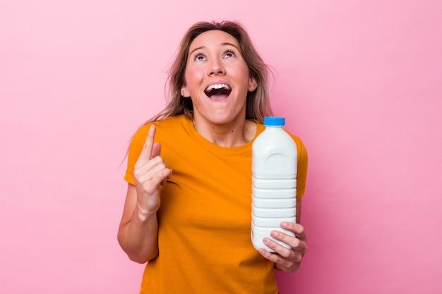 口を開けて逆さまを指しているピンクの背景に分離されたミルクのボトルを保持している若いオーストラリア人女性。