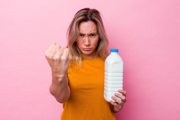 カメラに拳、攻撃的な表情を示すピンクの背景に分離されたミルクのボトルを保持している若いオーストラリア人女性。