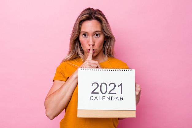 Молодая австралийская женщина держит календарь, изолированный на розовом фоне, хранит в секрете или просит молчания.
