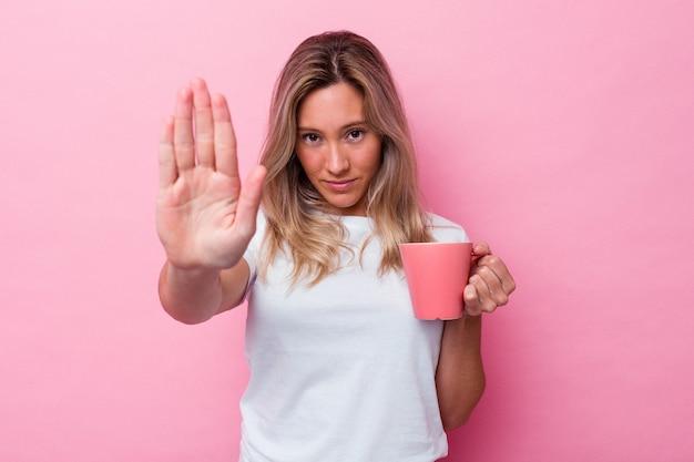 Молодая австралийская женщина держит розовую кружку, изолированную на розовом фоне, стоя с протянутой рукой, показывая знак остановки, предотвращая вас.