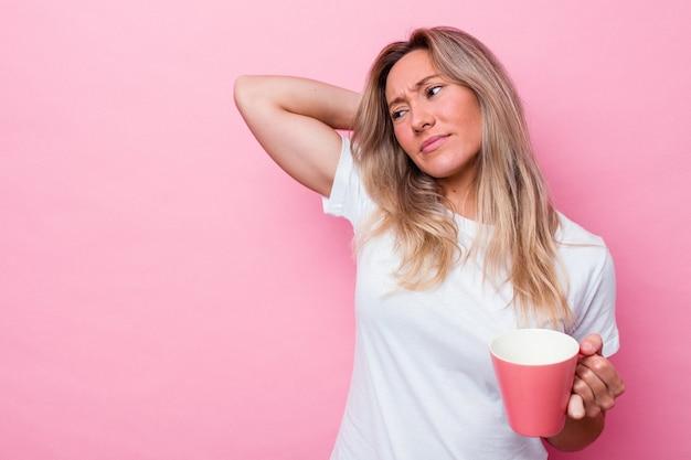 분홍색 배경에 격리된 분홍색 머그를 들고 머리 뒤쪽을 만지고 생각하고 선택하는 젊은 호주 여성.