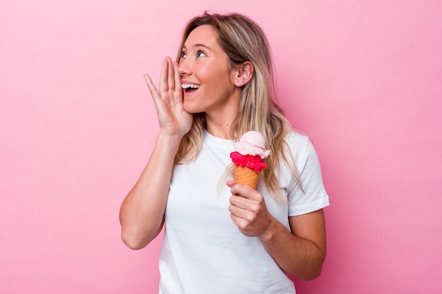 ピンクの背景に分離されたアイスクリームを持って叫び、開いた口の近くで手のひらを保持している若いオーストラリア人女性。