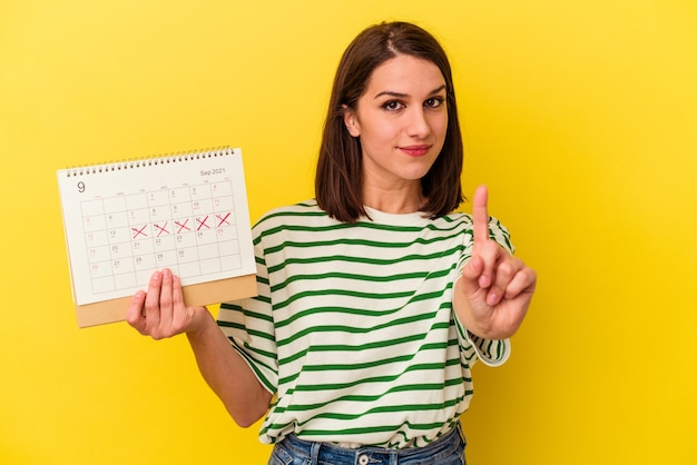 Young australian woman holding a calendar isolated on yellow background showing number one with finger.