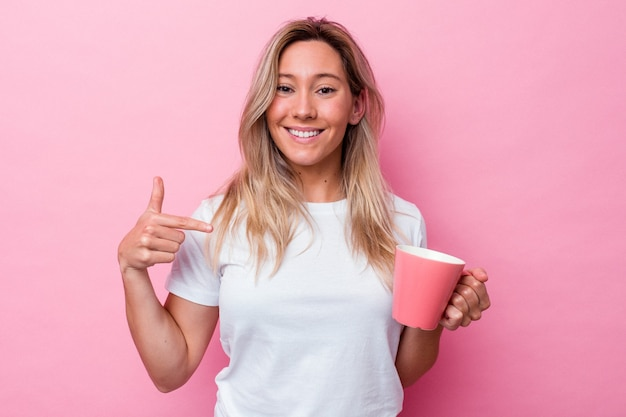 Young australian woman holding a pink mug isolated on pink background person pointing by hand to a shirt copy space, proud and confident