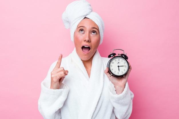 늦게 열린 된 입으로 거꾸로 가리키는 분홍색 배경에 고립 된 샤워를 떠나 젊은 호주 여자.