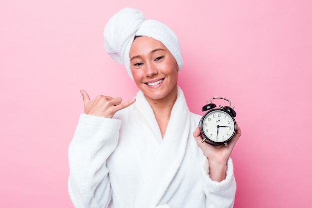 指で携帯電話の呼び出しジェスチャーを示すピンクの背景に分離されたシャワーを遅く離れる若いオーストラリア人女性。