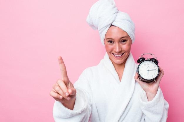 늦게 손가락으로 번호 하나를 보여주는 분홍색 배경에 고립 된 샤워를 떠나 젊은 호주 여자.