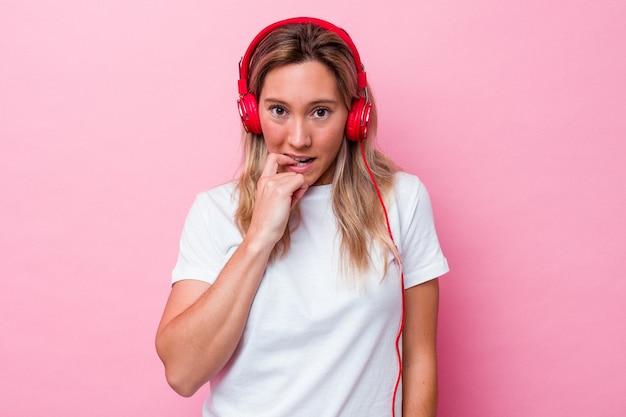 분홍색 배경에 격리된 음악을 듣고 있는 젊은 호주 여성은 손톱을 물어뜯고 긴장하고 매우 불안해합니다.