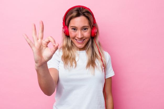 ピンクの背景に分離された音楽を聞いている若いオーストラリア人女性は、陽気で自信を持って大丈夫なジェスチャーを示しています。