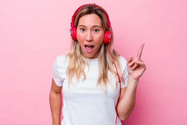 アイデア、インスピレーションのコンセプトを持つピンクの背景に分離された音楽を聞いている若いオーストラリア人女性。