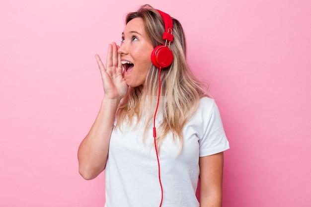 Молодая австралийская женщина слушает музыку, изолированную на розовом фоне, кричит и держит ладонь возле открытого рта.