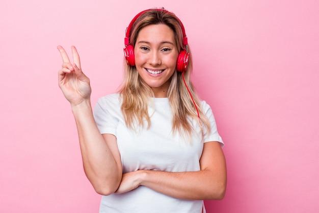 Молодая австралийская женщина слушает музыку, изолированную на розовом фоне, показывая номер два пальцами.