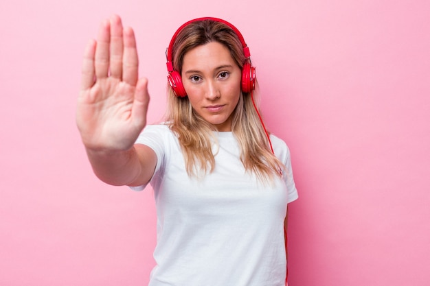 Молодая австралийская женщина слушает музыку, изолированную на розовом фоне, стоя с протянутой рукой, показывая знак остановки, предотвращая вас.