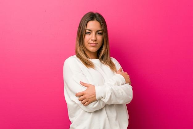 Молодые аутентичные харизматичные реальные люди женщина обнимает стену, беззаботно улыбаясь и счастливо.